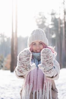 Winterfrau, die an einem kalten wintertag glücklich nach oben schaut und draußen im schnee lächelt.