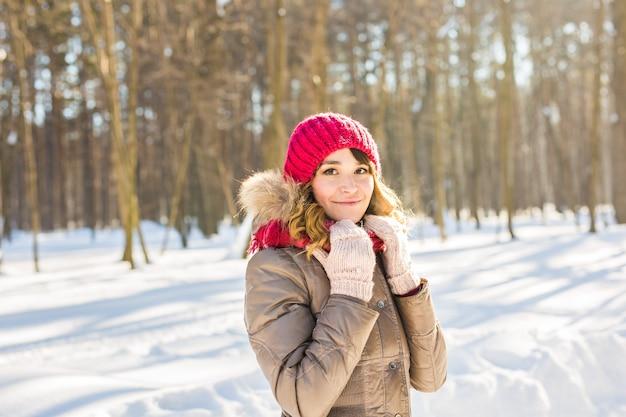 Winterfrau im schnee, der die kamera draußen an einem schneienden kalten wintertag betrachtet. kaukasisches weibliches modell des porträts draußen im ersten schnee
