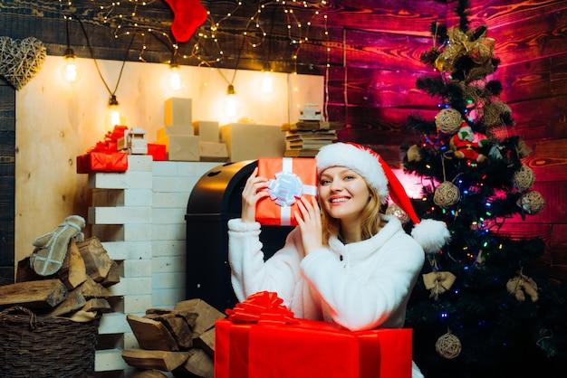 Winterfrau mit rotem weihnachtsmann-hut frohe weihnachten und guten rutsch ins neue jahr weihnachtsschmuck und...