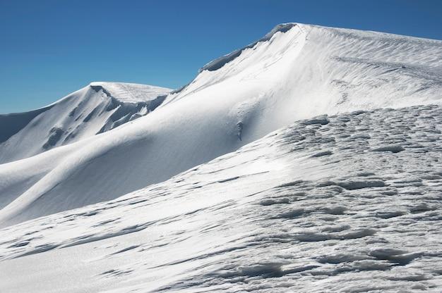 Wintergebirgskamm mit überhängenden schneekappen und snowboardspuren auf blauem himmel