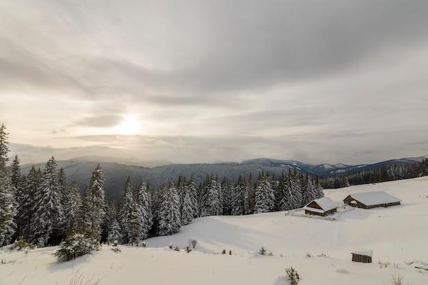 Wintergebirgslandschaft. alte holzhäuser auf schneebedeckter lichtung auf hintergrund des bergrückens, des fichtenwaldes und des bewölkten himmels. frohes neues jahr und frohe weihnachten karte.