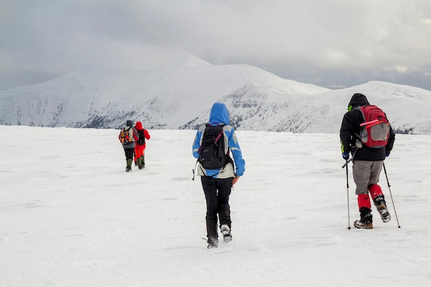 Wintergebirgslandschaft. drei reisende touristenwanderer in heller kleidung mit rucksäcken auf schneebedecktem feld, das in richtung des fernen berges auf bewölktem dunkelblauem stürmischem himmelkopierraumhintergrund geht.