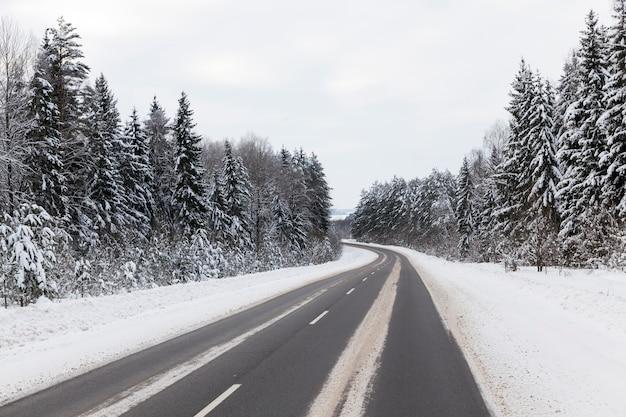 Wintergepflasterte straße für fahrzeuge, winterzeit bei schneewetter