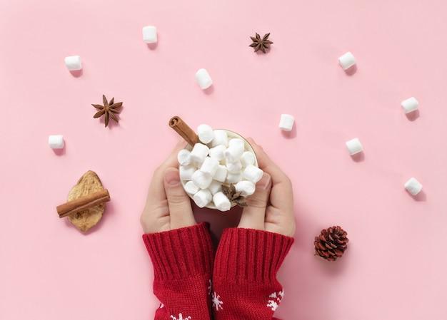 Wintergetränk weiße tasse mit marshmallows in weiblichen händen in gestricktem weihnachtspullover auf rosa