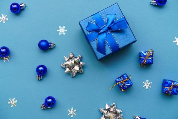 Winterhintergrund blaue süße geschenkbox mit blauen bandweihnachtskugeln in einer weihnachtszusammensetzung von ...