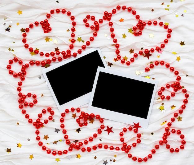 Winterhintergrund mit dekorativen funkelnden sternen, perlen und fotos. leere bilderrahmen für ihr bild oder ihren text.