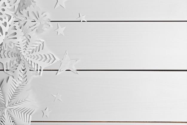 Winterhintergrund mit handgeschöpften papierschneeflocken auf hölzernem hintergrund