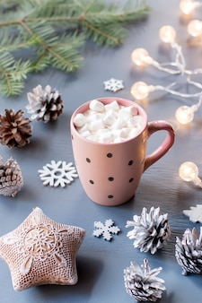 Winterhintergrund mit heißem getränk mit marshmallows, weihnachtsbeleuchtung, tannenbaum und dekorationen. platz kopieren, ansicht von oben