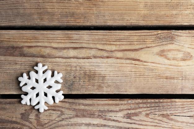 Winterhintergrund mit schneeflocke auf holzuntergrund