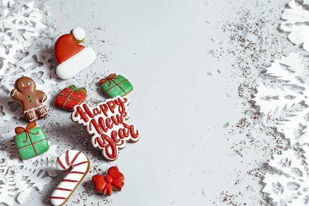 Winterhintergrund mit verziert mit glasurlebkuchen, schneeflocken und konfetti draufsicht. frohes neues jahr und weihnachtskonzept.