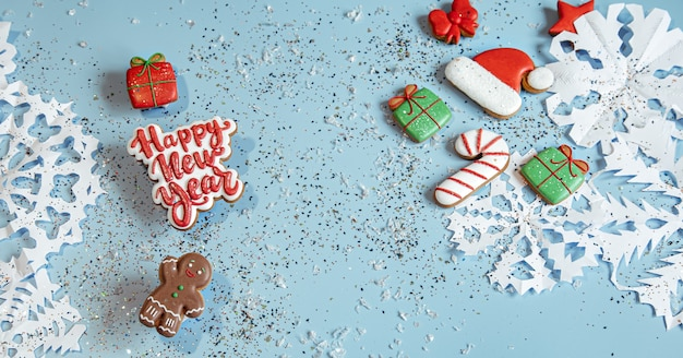 Winterhintergrund mit verziert mit glasurlebkuchen, schneeflocken und konfetti. frohes neues jahr und weihnachtskonzept.
