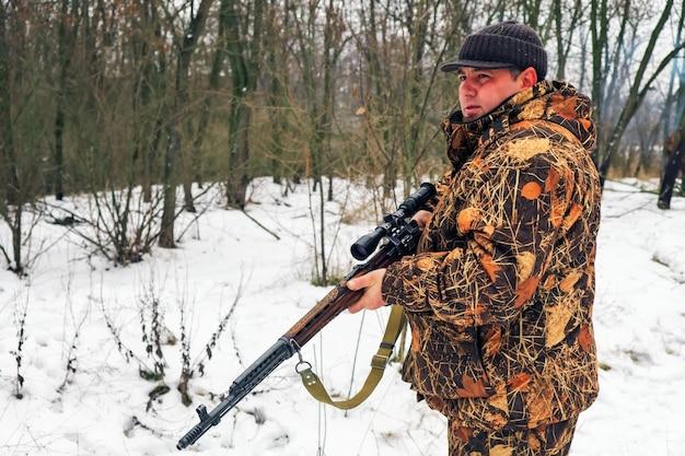 Winterjagd. jäger, der sich mit gewehr bewegt und nach beute sucht.
