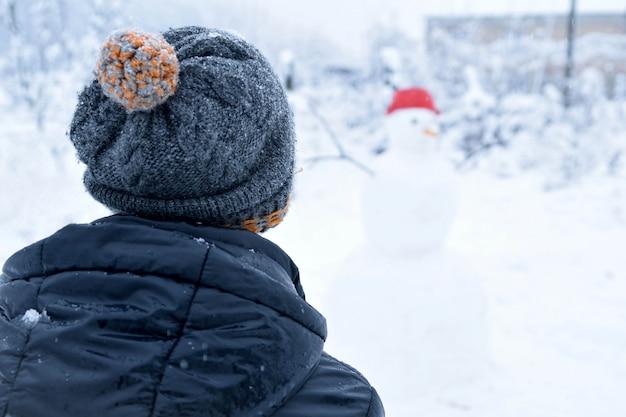 Winterjugendlicher in einer jacke und in einem hut formt einen schneemann auf einem winterhintergrund mit fallendem schnee in gefrorenem tageskonzept