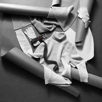 Winterkleidung. satz schöne helle unisex-kleidung auf grauem papier und schwarzer wand Premium Fotos