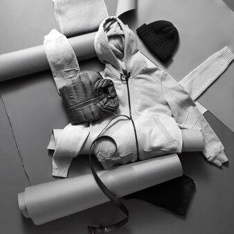 Winterkleidung. stellen sie gestrickte und warme winterkleidung auf ein graues konstruktionspapier und eine schwarze wand Premium Fotos