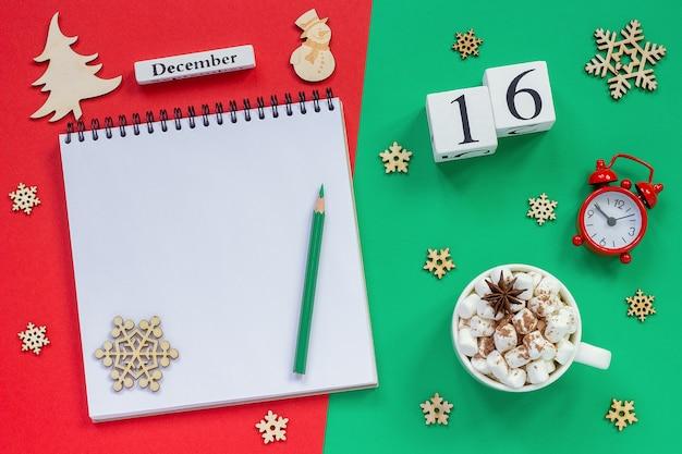 Winterkomposition. holzkalender 16. dezember tasse kakao mit marshmallow, leerer offener notizblock mit bleistift
