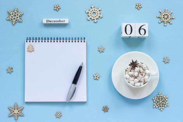 Winterkomposition. holzkalender 6. dezember tasse kakao mit marshmallow und sternanis, leerer offener notizblock