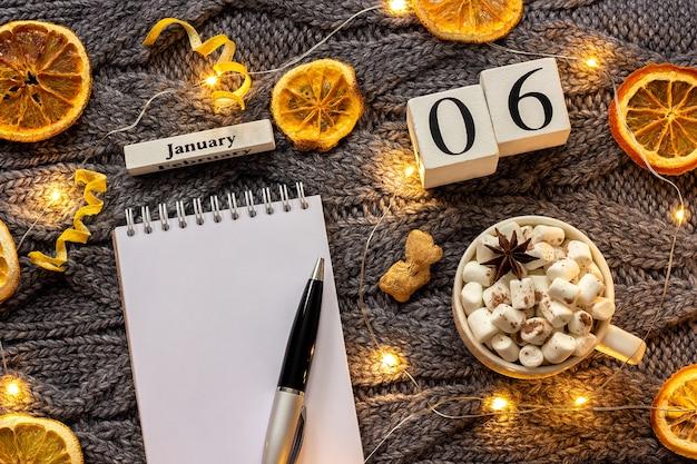 Winterkomposition. holzkalender 6. januar tasse kakao mit marshmallow, leerer offener notizblock mit stift, getrocknete orange