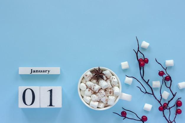 Winterkomposition. weiße hölzerne kalenderwürfel. daten 1. januar. tasse kakao mit marshmallows und dekorativem zweig