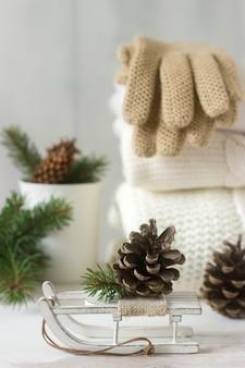 Winterkonzept mit weißem umfassendem pullover, handschuhen, schlitten, schale, kegeln und tannenzweigen.