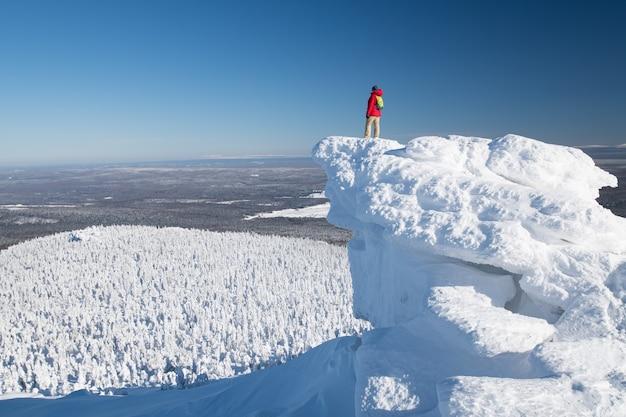 Winterlandschaft. bei winterkaltem, klarem wetter steht ein tourist auf einem berggipfel