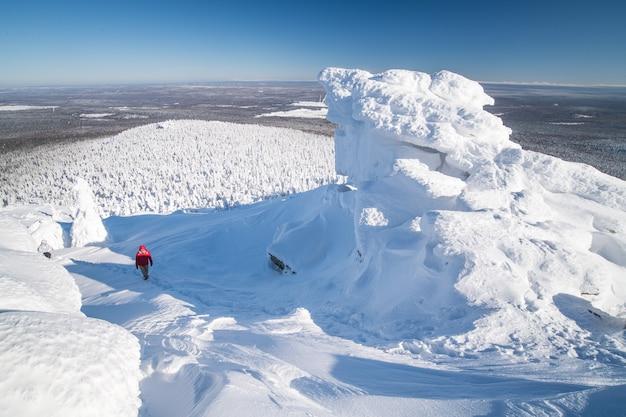 Winterlandschaft. ein tourist klettert bei winterkaltem, klarem wetter auf eine bergkette