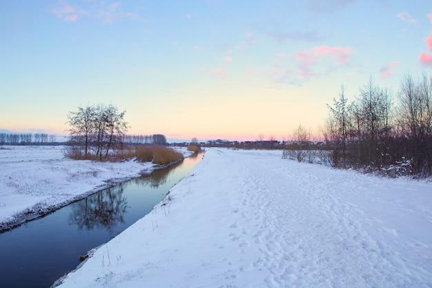 Winterlandschaft in den niederlanden mit schönem farbigem sonnenuntergangshimmel und frischem weißem schnee