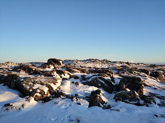 Winterlandschaft in island. ein mit moos bedecktes feld aus erstarrter lava ist mit schnee bedeckt.