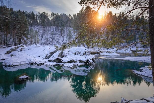 Winterlandschaft, kleiner eisfreier see in den bergen inmitten schneebedeckter wälder. bäume spiegeln sich im abendsonnenlicht im seewasser
