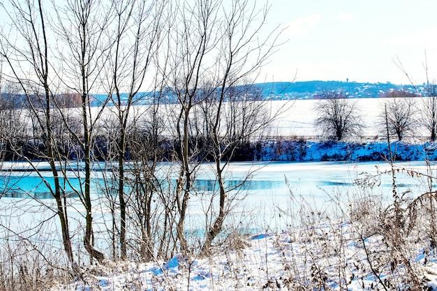 Winterlandschaft mit bäumen am fluss an einem sonnigen tag