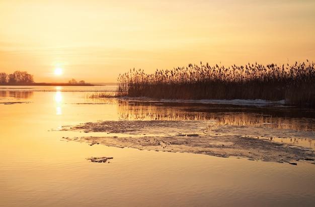 Winterlandschaft mit brennendem himmel des flusses und des sonnenuntergangs. schöne winterlandschaft. zusammensetzung der natur.