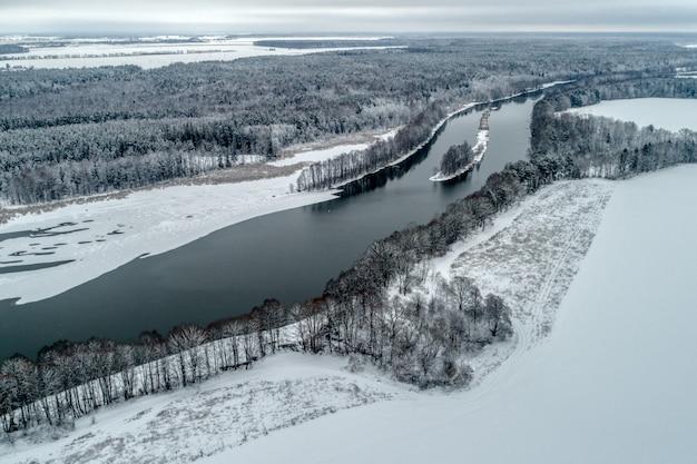 Winterlandschaft mit einem fluss, der durch den winterwald fließt.