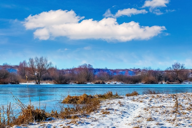 Winterlandschaft mit einem fluss und einer schönen weißen wolke im blauen himmel