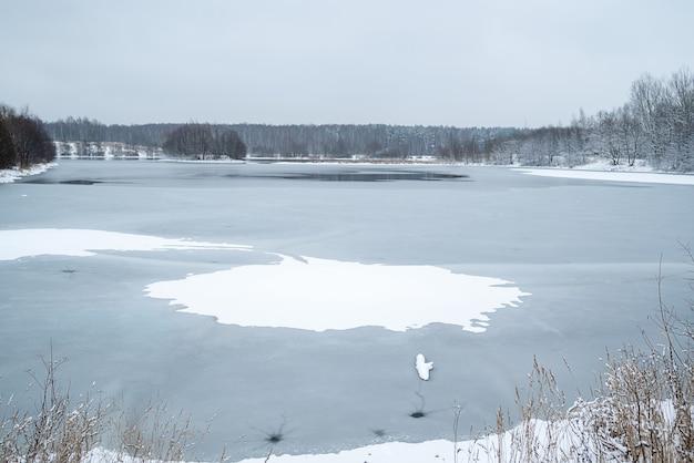 Winterlandschaft mit eisloch in der mitte des zugefrorenen sees