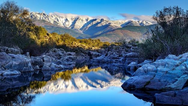 Winterlandschaft mit fluss, reflexionen im wasser und großen felsen.