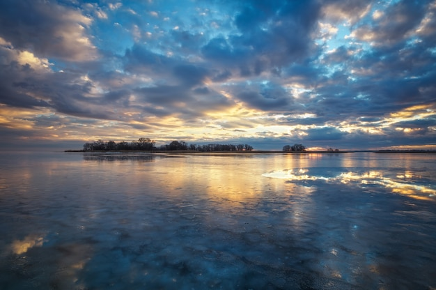 Winterlandschaft mit fluss, schilf und bewölktem sonnenuntergangshimmel. zusammensetzung der natur.