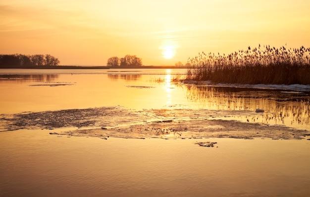 Winterlandschaft mit fluss, schilf und sonnenunterganghimmel. schöne winterlandschaft. zusammensetzung der natur.