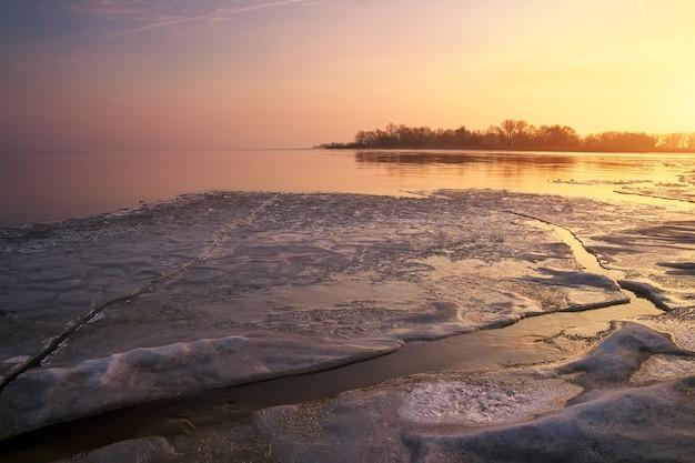 Winterlandschaft mit gefrorenem fluss und sonnenunterganghimmel.