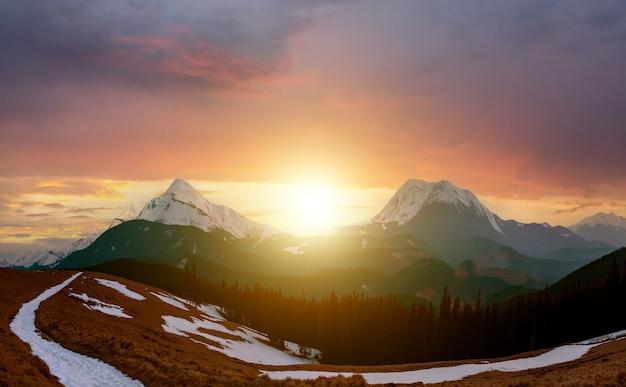 Winterlandschaft mit hohen gipfeln und nebligem tal unter lebendigem buntem sonnenuntergangabendhimmel in felsigen bergen.