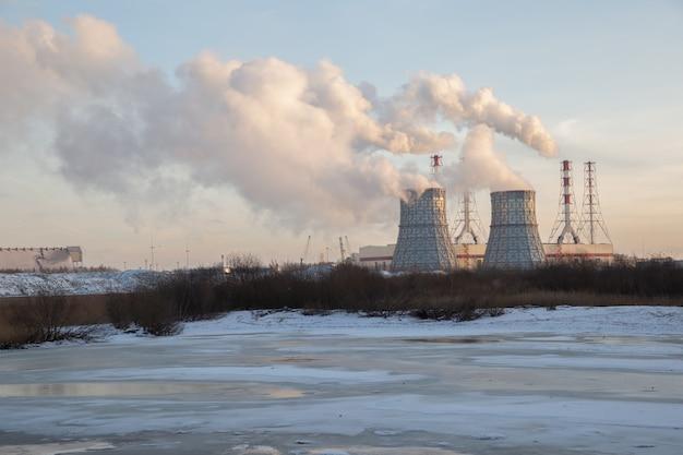 Winterlandschaft mit rauchenden schornsteinen des wärmekraftwerks