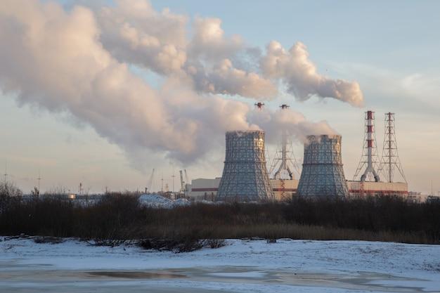 Winterlandschaft mit rauchenden schornsteinen heizkraftwerk