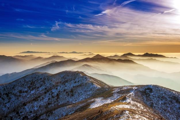 Winterlandschaft mit sonnenuntergang und nebel in den deogyusan bergen, südkorea