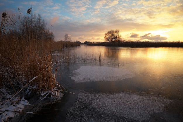 Winterlandschaft mit sonnenunterganghimmel und gefrorenem fluss. tagesanbruch