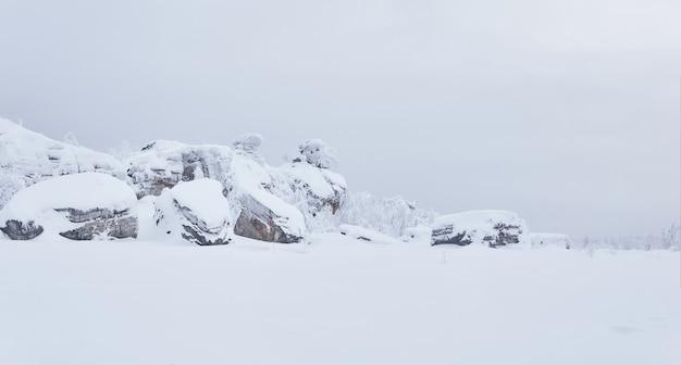 Winterlandschaft schneebedeckte granitfelsen inmitten weißer stille unter einem düsteren himmel