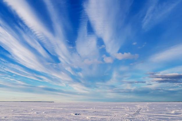 Winterlandschaft über gefrorenem fluss mit blauem hellem himmel und weißen wolken