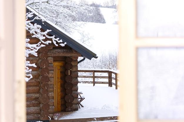 Winterlandschaftsansicht vom offenen fenster im holzhaus