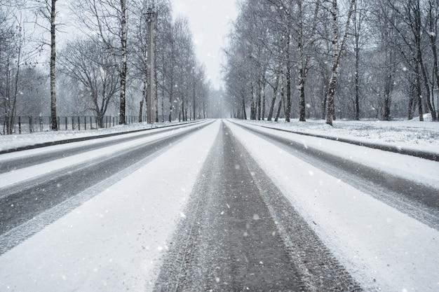 Winterlandstraße im schneefall. radspuren auf einer verschneiten straße