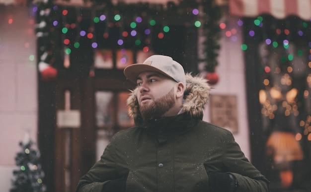 Winterlebensstilporträt des gutaussehenden mannes mit bart, der in der stadt geht