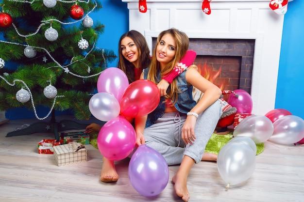 Winterlebensstilporträt von zwei schwestern, die zu hause nahe weihnachtsbaum sitzen und luftballons halten, bereit für feiertagsfeier. tragen sie helles make-up und kleidung. beste freunde, die spaß haben.