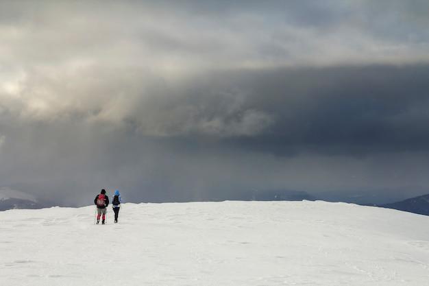 Winterliche berglandschaft. rückansicht von reisenden touristische wanderer mit rucksäcken auf schneebedecktem feld, die auf einem bewölkten dunkelblauen stürmischen himmelshintergrund am kalten wintertag in richtung des fernen berges gehen.